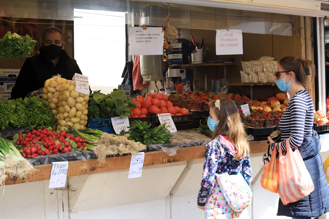Farmers' market image featuring fresh produce, a woman, child and farmer wearing protective masks.